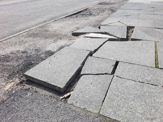 A pavement with broken and dislodged paving slabs.